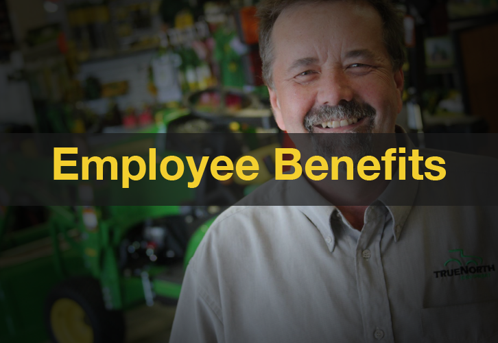 Employee smiling in front of John Deere equipment